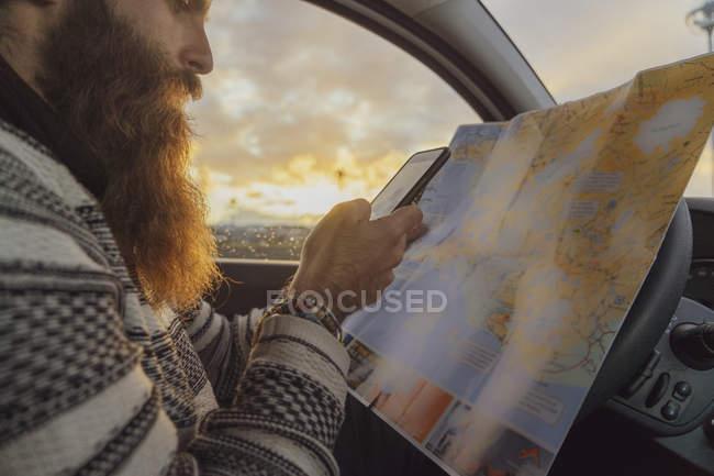 Homem que usa o smartphone no carro, olhando o mapa para sentidos — Fotografia de Stock