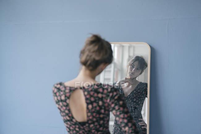 Junge Frau im Vintage-Kleid blickt in den Spiegel auf grauem Hintergrund — Stockfoto