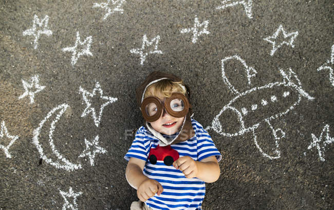 Portrait of smiling toddler wearing pilot hat and goggles, lying on asphalt painted with airplane, moon and stars — Stock Photo