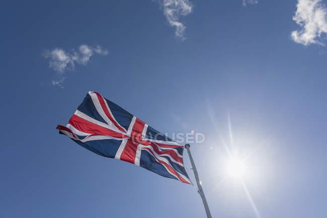 Union Jack no céu azul com luz de fundo — Fotografia de Stock