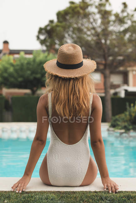 Rückseite Frau mit Strohhut am Pool sitzend, Rückseite — Stockfoto