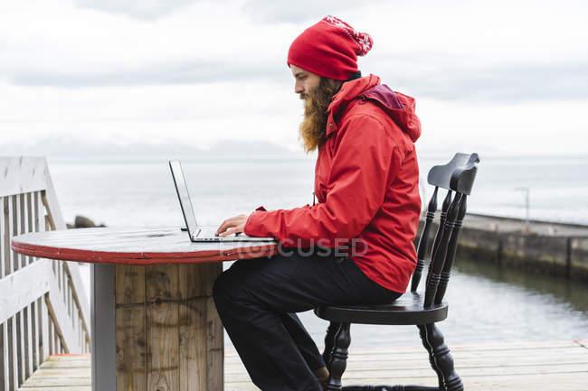 Islande, Nord de l'Islande, homme assis devant la mer avec un ordinateur portable — Photo de stock