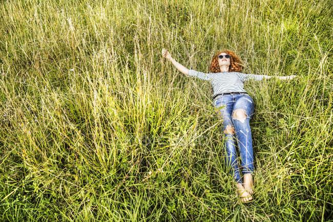 Молода жінка розслабляючий на зелений Луці — стокове фото