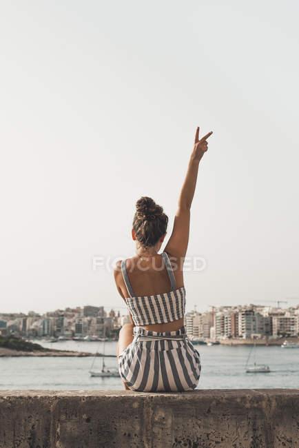Дівчинка-підліток носить Смугасте пляж знос, сидячи на стіні з піднятими ARM — стокове фото