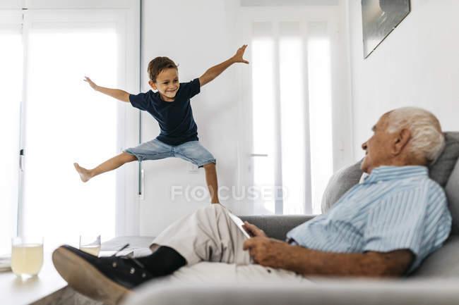 Abuelo sentado en el sofá con tableta viendo nieto saltando en el aire - foto de stock