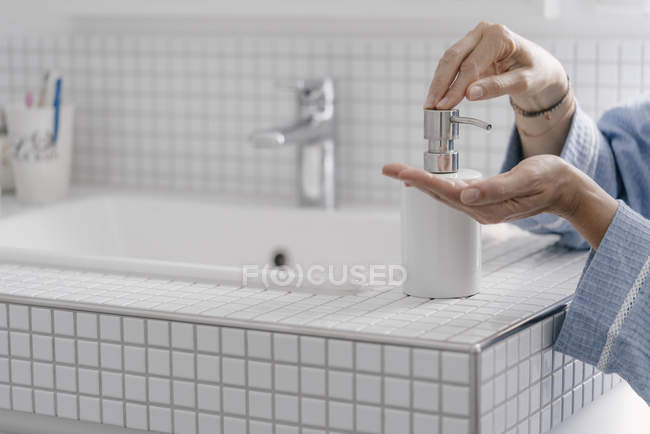 Close-up of female hands putting soap on hands in bathroom — Stock Photo