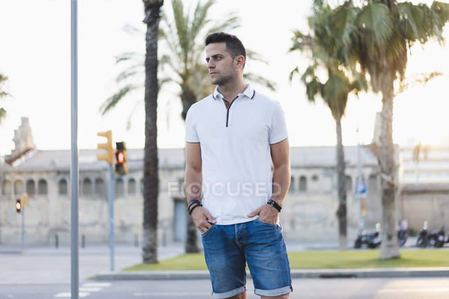 Young man standing on street with hands in pockets — Stock Photo