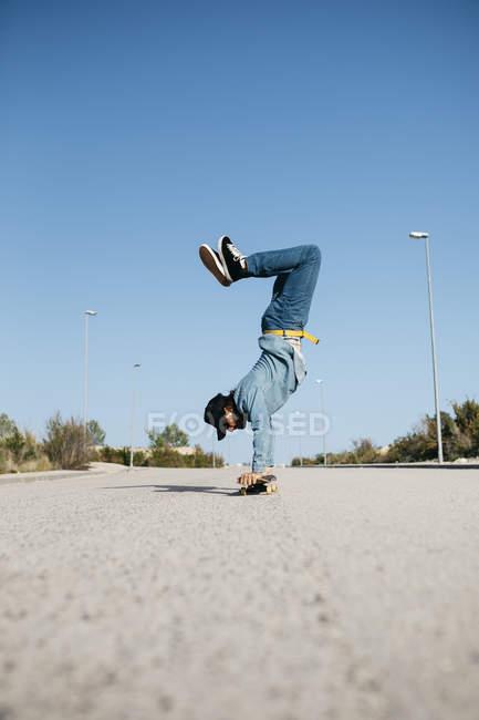Trendy man in denim and cap skateboarding, standing on skateboard upside down — Stock Photo