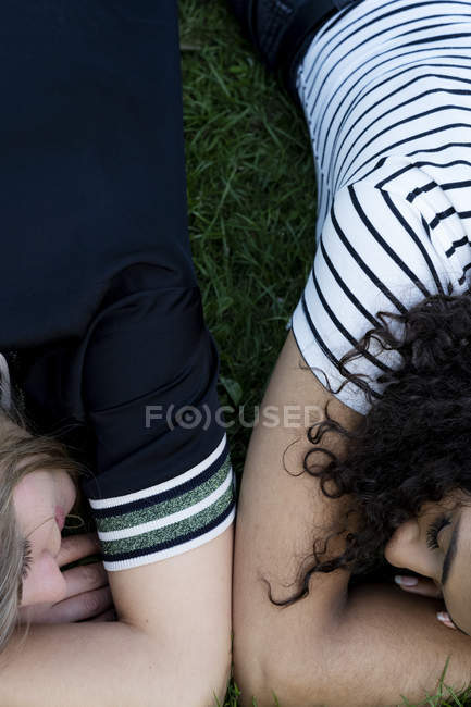Friends relaxing on grass in summer — Stock Photo