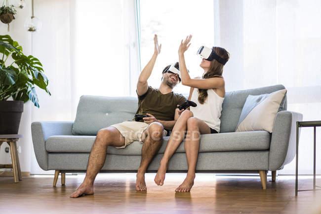 Coppia felice seduto sul divano a casa indossando occhiali Vr alta fiving — Foto stock