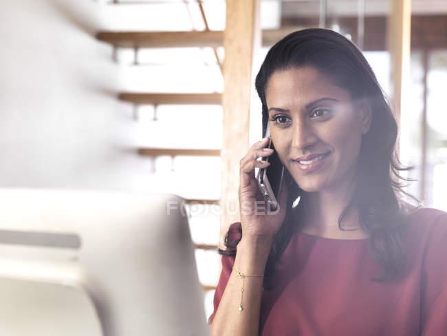 Портрет улыбающейся деловой женщины по телефону в офисе — стоковое фото