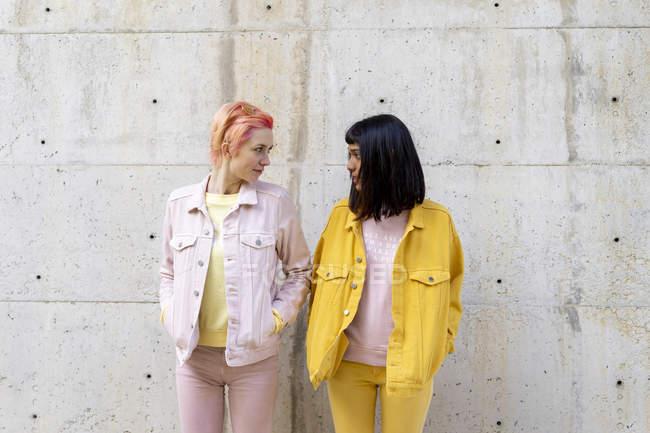 Два альтернативных друга весело провести время, носить желтые и розовые джинсы одежды, лицом к лицу — стоковое фото