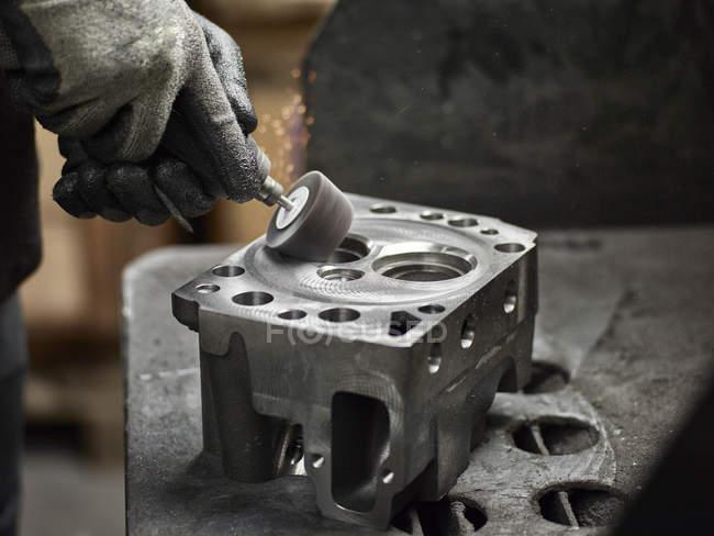 Worker in metalworking factory grinding cylinder head - foto de stock