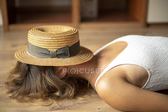 Unrecognizable young woman lying on floor with straw hat on head, covering face — Stock Photo