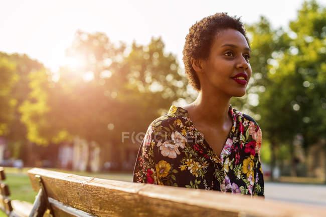 Jovem mulher no banco em um parque ao pôr do sol — Fotografia de Stock