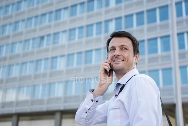 Empresário sorridente no celular da cidade — Fotografia de Stock