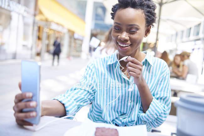 Portrait de femme souriante utilisant écouteurs et smartphone au café trottoir — Photo de stock