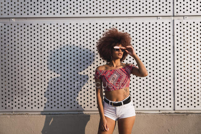 Portrait of fashionable woman wearing mirrored sunglasses against building wall — Stock Photo