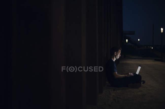 Mid adult man sitting cross-legged on ground, using laptop at night — Stock Photo