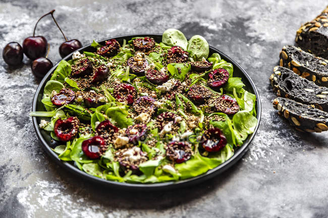 Lamb's lettuce with cherries, feta cheese, roasted sesame and black sepia spelt bread — Stock Photo