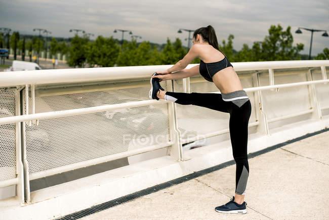 Спортивная женщина растягивает ногу — стоковое фото