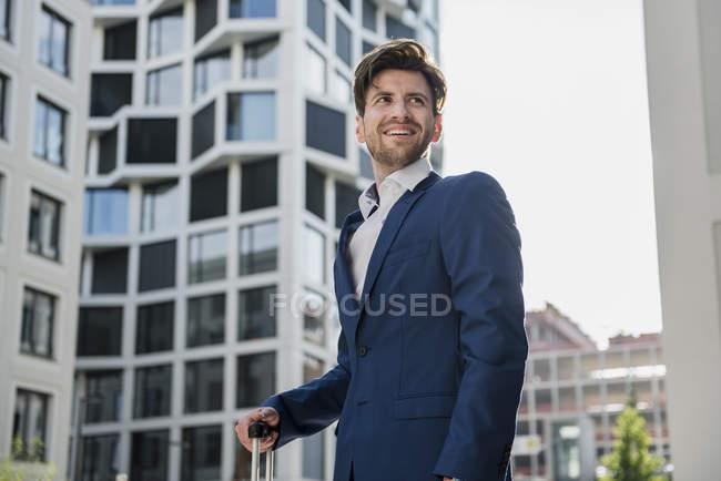 Улыбающийся бизнесмен с багажом в городе смотрит вокруг — стоковое фото