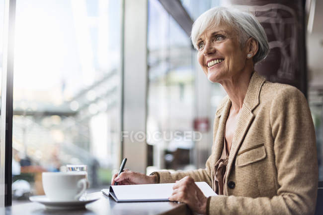 Улыбающаяся старшая деловая женщина делает заметки в кафе — стоковое фото