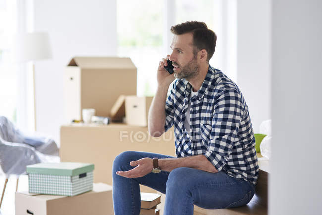 Serious man moving into new flat talking on cell phone — Stock Photo