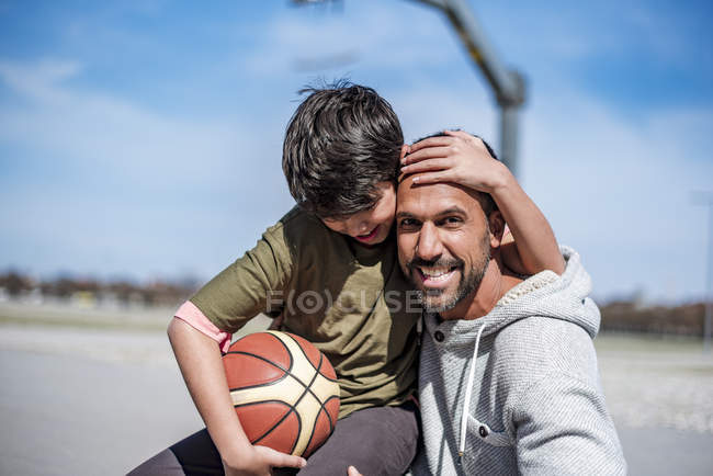 Portrait of happy father and son with basketball outdoors — стокове фото