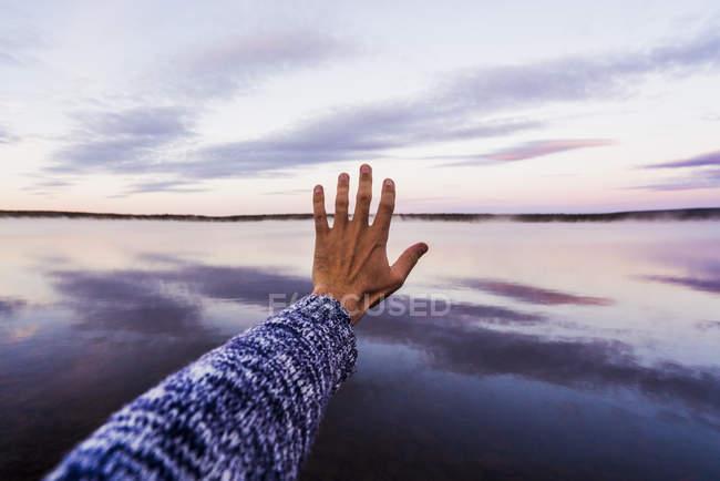 Mão de jovem chegando ao céu, reflexo púrpura do pôr do sol na água do mar — Fotografia de Stock