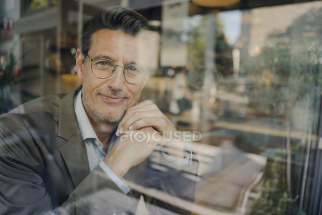 Reifer Geschäftsmann sitzt im Café und schaut aus dem Fenster — Stockfoto