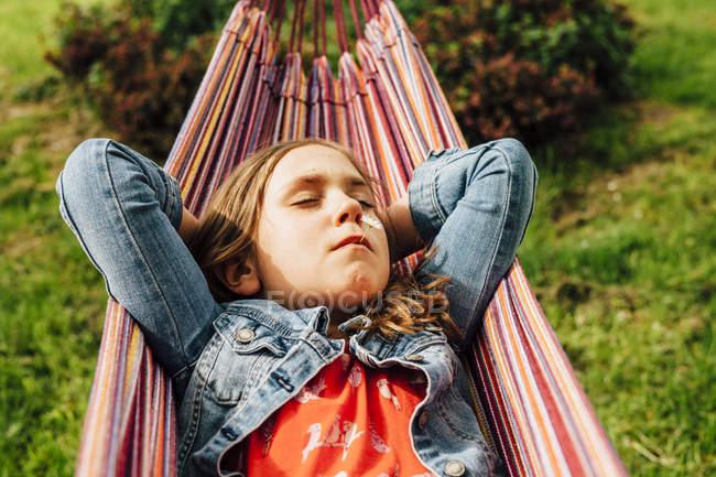 Портрет маленькой девочки, отдыхающей в гамаке — стоковое фото