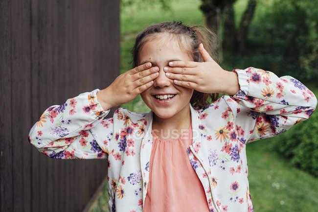 Retrato dos olhos de sorriso da coberta da menina com suas mãos — Fotografia de Stock