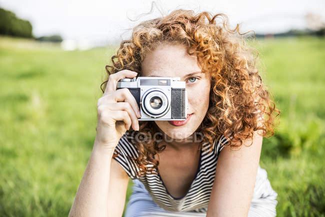 Jovem mulher tirando foto com câmera retro no prado verde — Fotografia de Stock