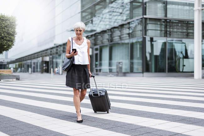 Donna anziana sorridente con i bagagli in movimento con il cellulare — Foto stock