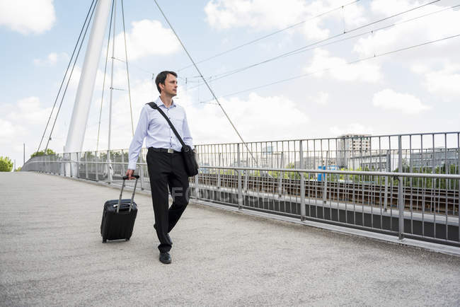 Businessman in the city with rolling suitcase crossing a bridge — Stock Photo