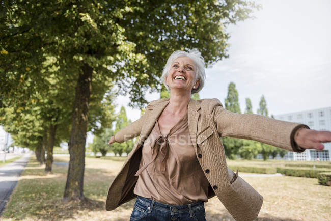 Happy senior woman with outstretched arms in park — Stock Photo