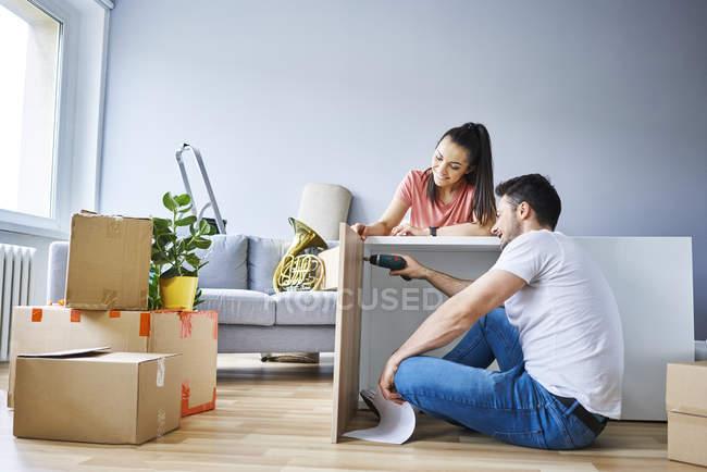 Casal em novo apartamento montar móveis juntos — Fotografia de Stock