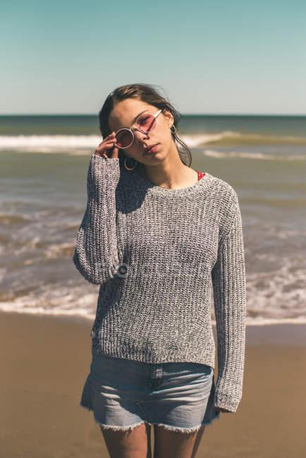 Espanha, retrato de uma jovem mulher usando óculos de sol em pé na praia — Fotografia de Stock