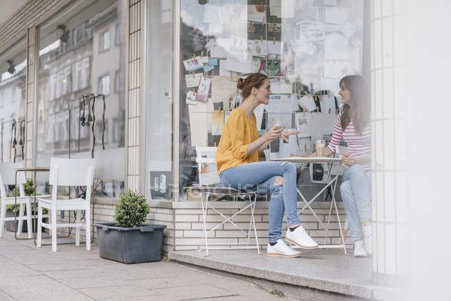 Two girlfriends meeting in a coffee shop and talking — Foto stock