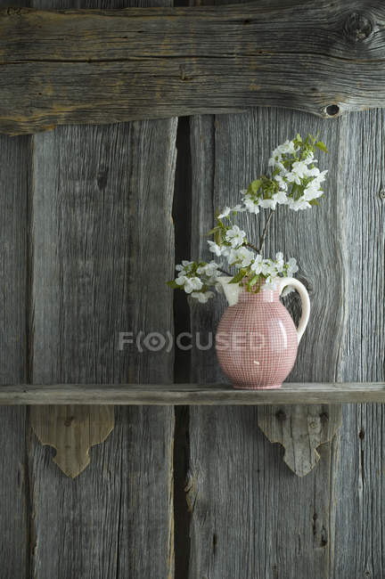 Twig of cherry blossoms in jar on shelf, in front of rustic wooden wall — Stock Photo
