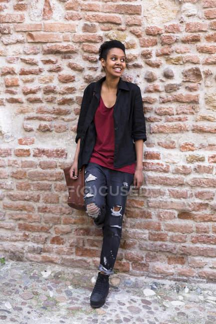 Портрет улыбающейся молодой женщины, прислонившейся к кирпичной стене — стоковое фото