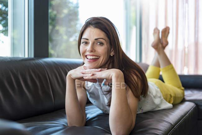Portrait de femme heureuse allongée sur le canapé à la maison — Photo de stock