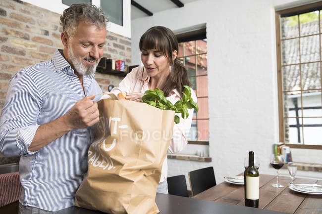 Mature man bringing grocery bag full of purchase to the kitchen — Stock Photo