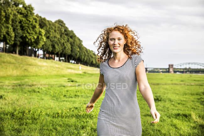 Portrait de jeune femme souriante courant sur la prairie — Photo de stock