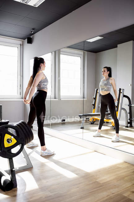 Woman exercising in gym looking in mirror — Stock Photo