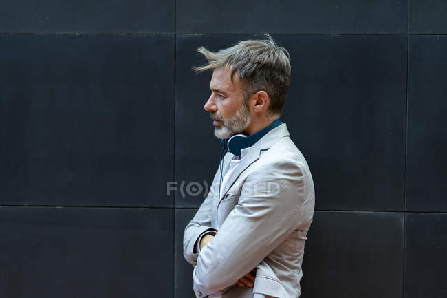 Бородатый бизнесмен с наушниками перед черной стеной — стоковое фото