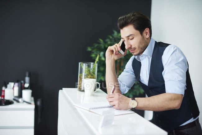 Парикмахер говорит по мобильному телефону, проверяя дневник — стоковое фото