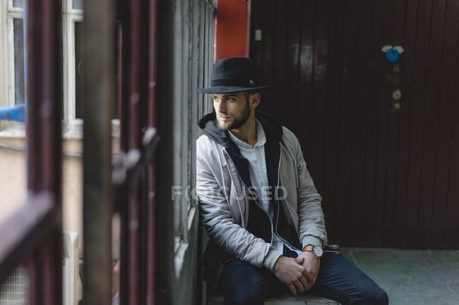 L'uomo barbuto con il cappello nero, guardando fuori dalla finestra — Foto stock