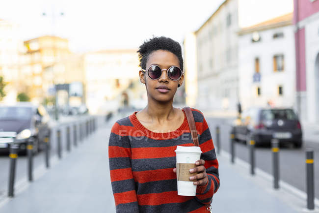 Portrait of young woman with coffee to go wearing sunglasses and striped pullover — Stock Photo